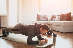 Free Young Ordinary Man Go In For Sport At Home. Full Size Pictrue Of Freshman In Workout And Beginner Guy Stand In Plank Royalty Free Stock Photo - 177490425