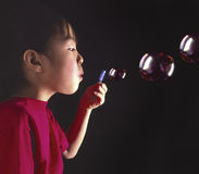 Young oriental girl blowing bubbles royalty free stock photos