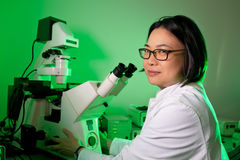 Young oriental scientist with microscope Royalty Free Stock Photos
