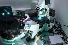 Young oriental scientist works with modern microscope Stock Photos