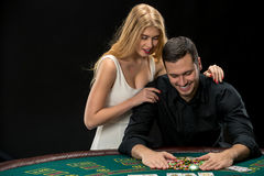 Young сouple playing poker. Man taking poker chips after winning Royalty Free Stock Images