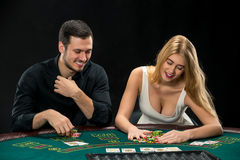 Young сouple playing poker, woman taking poker chips after winning Royalty Free Stock Image