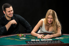 Young сouple playing poker, woman taking poker chips after winning Stock Photography