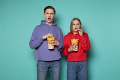Young outraged shocked couple in casual clothes watching contradictory movie, holding bucket of popcorn stock photo