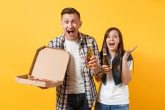 Young overjoyed couple woman man sport fans cheer up support team hold beer bottle italian pizza in cardboard flatbox. Young overjoyed couple women men sport royalty free stock photos