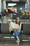 Young overjoyed traveler tourist woman holding paper map, search route, spread hands, wait in lobby hall at airport. Passenger traveling abroad on weekends royalty free stock photography