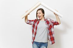 Young overjoyed woman in casual clothes holding wallpaper rolls above head in form of roof isolated on white background. Instruments, accessories for stock photography