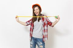 Young overjoyed woman in casual clothes, protective construction helmet holding toy measure tape isolated on white. Background. Instruments, tools for stock image