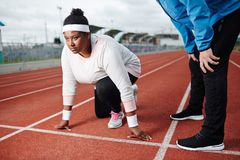 Woman on start. Young oversized sporty women standing by start line ready to run with her trainer near by Royalty Free Stock Image
