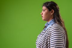 Young overweight beautiful Indian businesswoman against green background stock photo