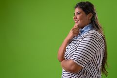 Young overweight beautiful Indian businesswoman against green background royalty free stock image