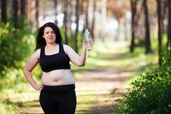 Young overweight smiling woman with a bottle of clear water outd. Overweight woman drinking water after jogging in the park. Portrait of young plus-size thirsty royalty free stock photos