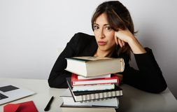 Young overwhelmed girl studying hard. Tired, stressed and overworked young woman student.Female model between a huge. Pile of books stock photography