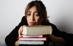 Young overwhelmed girl studying hard. Tired, stressed and overworked young woman student.Female model between a huge. Pile of books.Closeup view royalty free stock images