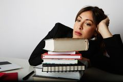 Young overwhelmed girl studying hard. Tired, stressed and overworked young woman student.Female model between a huge. Pile of books.Closeup view royalty free stock image