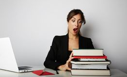 Young overwhelmed girl working hard. Young woman student shock of many books.Female model front of huge pile of books. royalty free stock photos