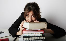 Young overwhelmed woman studying hard. Tired, stressed and overworked young student.Female model between a huge pile of. Books royalty free stock images