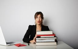 Young overwhelmed woman working hard. Young woman student shock of many books.Female model front of huge pile of books. Young overwhelmed woman working hard royalty free stock photo