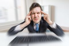 Young overworked man is tired by working with compuiter and suffering from headache Stock Image
