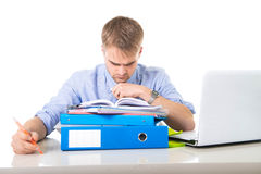Young overworked and overwhelmed businessman in stress leaning on office folder exhausted and depressed stock photo