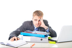Young overworked and overwhelmed businessman in stress leaning on office folder exhausted and depressed Stock Image