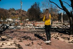 Woman looking at her burned home after fire disaster stock image