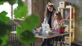 Young owners of small business are working with laptop in modern loft style office. Blonde is sitting and typing. Brunette is standing near the desk and stock video footage