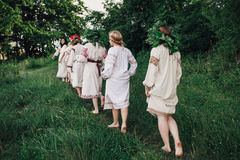 Young pagan Slavic girl conduct ceremony on Midsummer. Earth Dayю Girls in the Ukrainian attire sitting against the backdrop of the river in wreaths of Stock Photo
