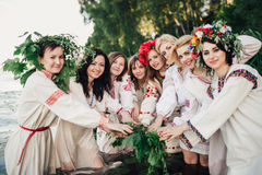 Young pagan Slavic girl conduct ceremony on Midsummer. Earth Dayю Girls in the Ukrainian attire sitting against the backdrop of the river in wreaths of Royalty Free Stock Photography