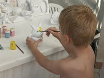 Young Painter. Five years old boy painting a toy Stock Photography