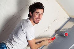 Young painter. Smiling young man painting the wall Royalty Free Stock Photos