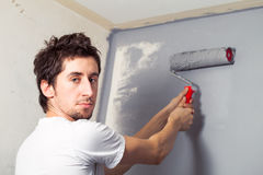 Young painter. Young man paints a wall with a gray paint Royalty Free Stock Image
