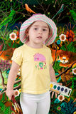 Young Painter. Young girl / toddler with new paints and brushes in her hand in front of painting with jungle elements royalty free stock photo