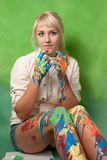 Young painter covered with paint on a bright green background Royalty Free Stock Images