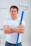 Young painter with crossed arms holding paintroller and looking Royalty Free Stock Image