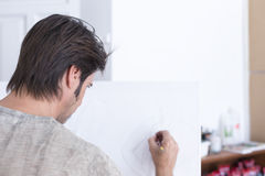 Young painter drawing on canvas - painting session. Back view of a man drawing with a pencil on canvas at his painting studio - focus on the eye stock photos