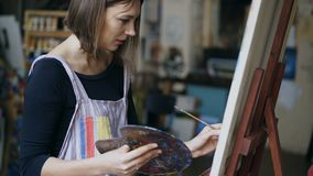Young painter girl in apron painting still life picture on canvas in art-class royalty free stock photo