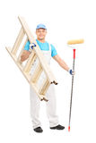 Young painter holding paint roller and a ladder Stock Image