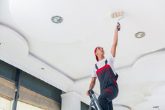 The young painter painting the ceiling in construction concept Stock Photos