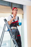 The young painter painting the ceiling in construction concept Royalty Free Stock Photos