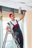 The young painter painting the ceiling in construction concept Stock Photography