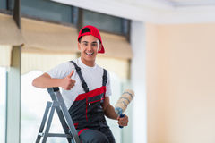 The young painter painting the ceiling in construction concept Royalty Free Stock Images