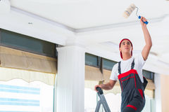 The young painter painting the ceiling in construction concept Royalty Free Stock Image