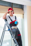 The young painter painting the ceiling in construction concept Stock Photo