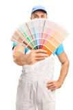 Young painter spreading a color swatch. Vertical shot of a young male house painter holding a color swatch isolated on white background with the focus on the royalty free stock images