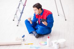 The young painter trying to match colours for painting job. Young painter trying to match colours for painting job Royalty Free Stock Images