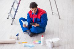 The young painter trying to match colours for painting job. Young painter trying to match colours for painting job Stock Images