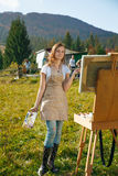 Young painter at work in the mountains Stock Photography