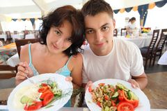 Young pair in cafe with plates with salad Stock Images
