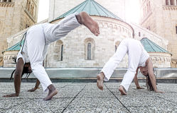 Young pair capoeira partners performing kicks outdoor Royalty Free Stock Images